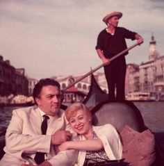 Italian film director Federico Fellini and his wife, actor Giulietta Masina, hold hands and smile while sitting in a gondola with a gondolier rowing in the background, Venice, Italy. circa: 1955