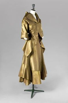 Callot Soeurs Summer 1914 Haute Couture. Bronze taffeta, jacket with shawl collar and asummetrical hem, secured with a black velvet bow in the back.
