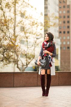 over the knee burgundy boots, gray dress, light gray coat, and over sized plaid scarf