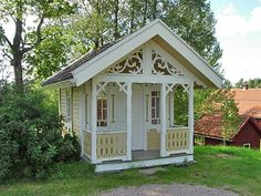Her Favorite little cottage. Porch, gable end, windows on either side of doors...would really like multi-x's on windows. Likes the scroll work on the gable. Small curved knee brace where posts meat beam on porch.