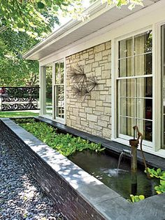 Placing a raised pond abutting the house under windows makes it visible from both inside and out.
