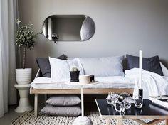 Sofa bed in a beautiful small Swedish space in calm greys. Stadshem / Jonas Berg / Joanna Bagge.