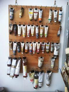 Use um painel de madeira, alguns ganchos e grampos para manter os tubos de tinta em ordem e por perto - Ademilar