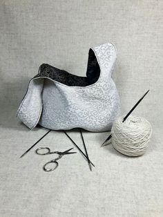Elegante Knotentasche mit zarten ornamentalen Rankenmuster für Strickprojekte oder Häkelarbeiten. Diese Tasche ist schwarz-messing auf der einen,