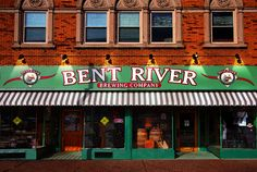 Located in downtown Moline, Illinois in the Quad Cities, Bent River Brewery beers flow from the beautifully polished Bohemian Brah Haus copper kettles and today, Bent River produces over 1500 barrels of award winning beers annually and they have garnered yearly awards at brew competions throughout the midwest, including a second place finish at the world renowned Great American Brew Fest! Great beer, great food, outdoor seating, special events and live music.