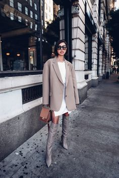 Obsessed with oversized blazers lately - love this neutral one. Paired it with a white shirt dress, neutral tall leather boots, leather shoulder bag, and Bottega Veneta sunglasses #outfit #outfitidea #fashion #style #leatherboots #blazer #oversizedblazer #shirtdress