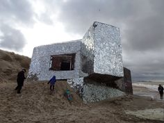 a world war 2 bunker covered with shards of broken mirror on the beach in Dunkirk, France