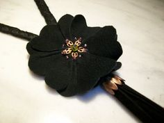 Long black braided plaited silk necklace with a black suede flower on Etsy, $53.00
