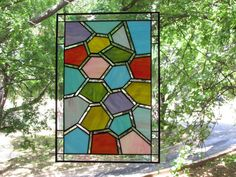 This beautiful stained glass panel is made in a random honeycomb design. There are 83 pieces of glass and the glass is opaque pastels surrounded by iridescent wavy clear glass. The border is also the iridescent clear wavy with 8 - 1 square bevels. The panel has a 1/4 zinc border and the entire panel is finished with a black patina.  Panel can hang either indoors or outdoors and can hang either horizontally or vertically. I will supply 2 of silver chain.  Measures approximately 14 1/2 x 21.