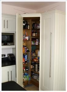 corner walk-in larder cupboard from bespoke kitchen designed by Cameron Pyke of Celtica Kitchens by Celtica Heritage. Cabinet in high quality birch multi-ply with solid oak edging.