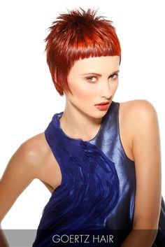 Cropped bangs and a captivating red hair color form the foundation of this exotic short cut and ups the glamour factor of this bold 'do.