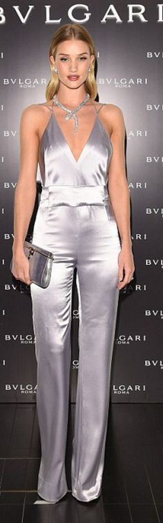 Who made Rosie Huntington-Whiteley's jewelry, clutch handbag, and gray satin jumpsuit?