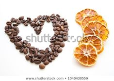 Coffee heart from beans and dried orange slices on white background