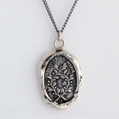 Integrity Talisman Necklace This French handcrafted wax seal necklace reads Toujours le Meme which means Always the Same. The jasmine branches represent devotion and constancy.