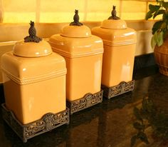 """Mustard Yellow Pineapple Top Kitchen Canister Set            Only ONE Mustard Yellow Kitchen Canister Set left in stock! A symbol of welcoming! Greet your guests with warmth and hospitality.  Set of three Pineapple Ceramic Canisters in a beautiful yellow finish resting  in an attractive rust base with matching Pineapple Lid Finial. Your kitchen or bar counter will be beautiful with these additions! Large  Size: 16 1/2"""" Tall X 7 1/2"""" X 7 1/2"""". Medium canister: 15 1/2"""" Tall X 7  1/2..."""