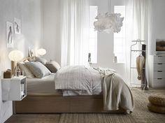 Ein helles Schlafzimmer mit MALM Bettgestell hoch mit 4 Schubladen in Eichenfurnier weiß lasiert
