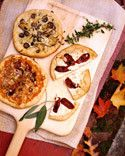 The dough can be made the night before and then formed into rounds just before the party. Set out a variety of toppings in bowls, and let guests assemble their own pizzas before baking them. We particularly like roasted tomatoes with fresh mozzarella cheese, and thinly sliced baby artichokes and eggplant with grated Asiago cheese. Pureed butternut squash, caramelized red onions, grated fontina cheese, and toasted pumpkin seeds make for an unexpected but perfectly delicious autumnal pie.
