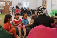 Syrian refugee children listen to stories at the community services centre run by CARE International at Azraq refugee camp.