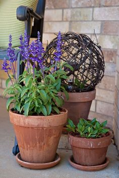 simple porch decor...grape vine ball with a solar light inside of it, in a pot..cute..illuminate the flowers at night, looks neat during the day!