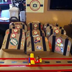 Flipawoo designed luggage sign anf luggage tags, party favor boxes and world destination stickers from amazon.con, brown kraft paper from walmart, red and silver duck tape, and a mickey mouse airplane from walmart as well...