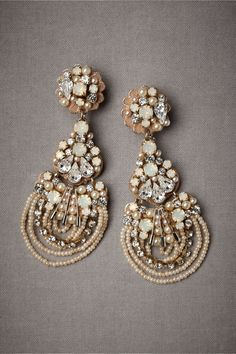 """Out-of-the-Blue Earrings. A triton of SAFETY PINS makes an unexpected yet intriguing appearance amongst glittering crystals, scallops of brass and arcs of milky seed beads. From Rada. 3.75""""L, 1.5""""W. Crystals, brass, seed beads, safety pins. Handmade in Spain."""