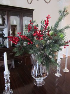 A vase of red berries and pine is the perfect Christmas centerpiece for your table. Come see my dining room decked for the holidays and all the ways I decorated my home for Christmas here!