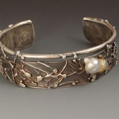 "Cuff Bracelet by Javita Harris-Casey.  ""One inch sterling silver bracelet accented with south sea pearl. Choice of stones, pearls or your special objects to be set or wrapped onto the bracelet"""