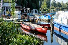 5420 Bootsvermietung am Stadtsee von Mölln - ein rotes Kanu liegt am Schilf des Sees - im Hintergrund Tretboote.   Flickr - Fotosharing!