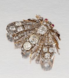 RUBY AND DIAMOND BROOCH/PENDANT, LATE 19TH CENTURY Designed as a moth, its wings, thorax and head set with circular-, rose-cut and cushion-shaped diamonds, its eyes highlighted with circular-cut rubies, later bale and brooch fitting, case.