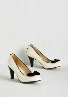 Make each step as spirited as your upbeat attitude by donning these cream-colored heels for your next special occasion. With tuxedo-inspired style, these vegan faux-leather midis by T.U.K. tout black scallops and a velvety details like decorative buttons on the heels and a bow on each toe. Tres chic!