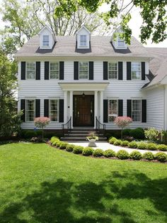 Beautiful #dormers and shutters adorn this adorable #colonial #home. Especially love the lush #landscaping!