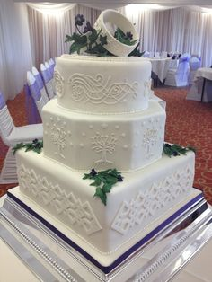 """Lord of the Rings inspired wedding cake. Inspiration for Base tier - Killi's cloak trim.  Centre tier - White Tree of Gondor.  Top tier - Arwen's Dress sleeve embroidery.  The Rings are embellished with the quote from the Film - """"I would rather share one lifetime with you than face all the ages of this world alone""""  - written in Elvish script."""