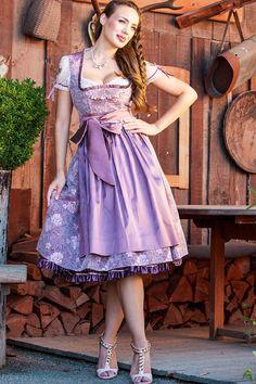 """""""Violetta"""" von El Picaflor ist ein atemberaubendes Couture Dirndl in Misty Mauve. Eine schimmernde Seidenschürze und die eingewebten Rosenblüten intensivieren das edle Design. Der erstklassige Schnitt gepaart mit dem Charivari aus Perlen- und Blumenanhängern volllenden das lilafarbene Desinger Dirndl!"""