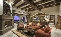 Tuscan Family Room open to the kitchen with Red Living Room Furniture and a Large Metal Mirror above the fireplace mantel.