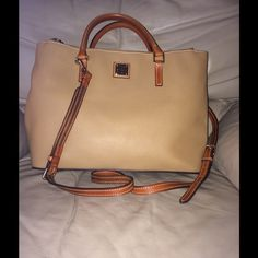 """Dooney & Bourke Pebbled Leather Satchel Authentic Dooney & Bourke Willa Satchel tan with carry handles & adjustable shoulder strap. Large middle section with zipper pocket along one-side & 2 smaller pockets for cell phone. Two zipper sections on the outside of the purse. Shoulder strap is adjustable, middle section of the strap can be removed. Feet on bottom, snaps on side to make purse larger. Dimensions- length-15"""", height-10"""", width-6"""" Dooney & Bourke Bags Satchels"""