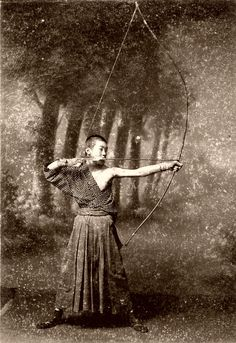 A young Archer holding his bow in the Kai (full draw) position.   The stippling on the photograph is caused by the acidic cardboard mount eating into the image.