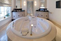 An enormous jacuzzi bath in the middle of the master suite's bathroom, with his and her sinks and a walk in double shower beyond it