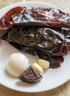 Authentic Enchilada Sauce Recipe - dried chilies, onion, garlic and chocolate on a white plate - Authentic Enchilada Sauce, Sauce Enchilada, Recipes With Enchilada Sauce, Homemade Enchilada Sauce, Homemade Enchiladas, Sauce Recipes, Cooking Recipes, Freezer Recipes, Gourmet