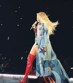 Queen Beyoncé wearing a custom #RobertoCavalli total look designed by Peter Dundas while performing at The Formation World Tour in Stockholm, Sweden. The look is made of a leather, denim and printed silk patchwork and embroidered denim coat; worn over a black silk lace and denim jeans bodysuit with multicolor velvet applications embroidered with crystal and tribal decorations. The look is accessorized with a pair of thigh high red patent platform boots.