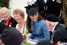 All smiles: The Duchess appeared to be enjoying her time at the tea party - laughing and chatting to one veteran to her left