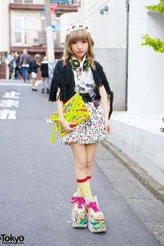 This is Moriya Kuma, you might recognize her from her participation in many of the Harajuku Fashion Walk events.  Moriya Kuma's cheetah print shirt and geometric skirt are both from Goocy, while her fringe jacket is a resale from New York Joe Exchange. Her look also includes an H&M clutch which she altered herself, a panther tote bag, and painted Buffalo platforms. Her cross necklace is H&M. We also noticed a corset belt, cherry headpiece, neon headphones and sunglasses.