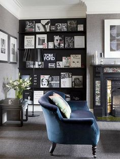 Love this gallery wall of coffee table books! In the back room by the fireplace