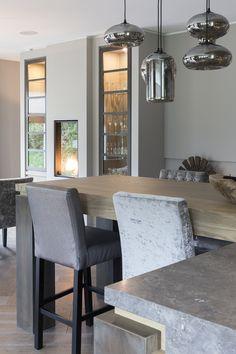 """De keuken is op maat gemaakt. De eikenhouten keukenkasten worden gecombineerd met een marmeren blad. De keuken heeft een bar. De barkrukken zijn in verschillend materiaal, wat zorgt voor een speels effect. Foto: Anneke Gambon – """"Stijlvol Wonen"""" - © Sanoma Regional Belgium N.V."""