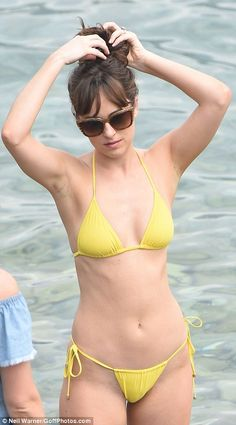 Making waves: The 26-year-old sizzled in a barely-there lemon bikini, which left very little to the imagination, as she joined co-star Jamie Dornan and his wife on the pebbled bay in France