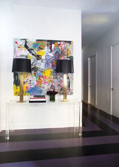 The floors in this NYC apartment mixed with the abstract art add color and creativity to the bland walls.