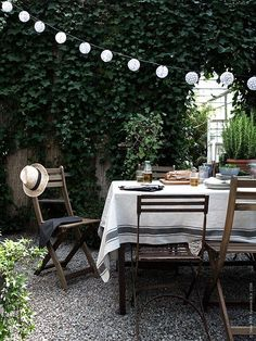 Outside patio for entertaining with string lights, wooden picnic bench, and natural linens.