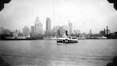 Detroit skyline with passenger ships and pre-Ambassador Bridge passenger/auto ferries.  1920's