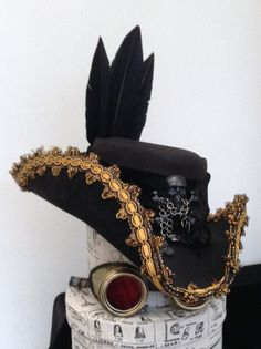 Water proofed Black leather tricorn with gold braid trim outside and inside, rear silk triple bow and tails, black velvet band, centre ornament of black