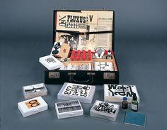"""Fluxus Collective's 'Flux-kit' from 1965/1969. Black vinyl attache case with 'Flux-kit"""" silkscreened in white on the lid; red cloth lines the interior of the case and contains: George Brecht, Games & Puzzles; Ben Vautier, Fluxholes; Robert Watts, Rocks Marked by Weight; Dick Higgins, Invocations of Canyons and Boulders for Stan Brackage; Benjamin Patterson, Instruction No.2; George Brecht, Games & Puzzles/Name Kit; Eric Anderson, 50 Opera; Nam June Paik, Zen for Film; Takehisa Kosugi…"""