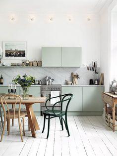 Cuisine en pastel et marbre, table en bois et chaises dépareillées
